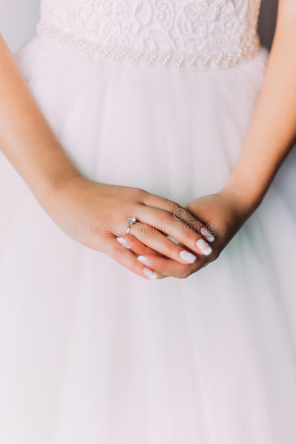 Close-up photo of beautiful woman's hands with bridal ring laying on a white dress stock photography