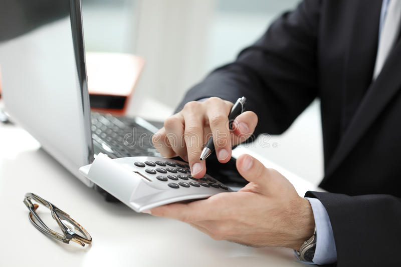 Close-up photo of a businessman analyzing financial data. Close-up of financial advisor analyzing data in office. Business people stock image
