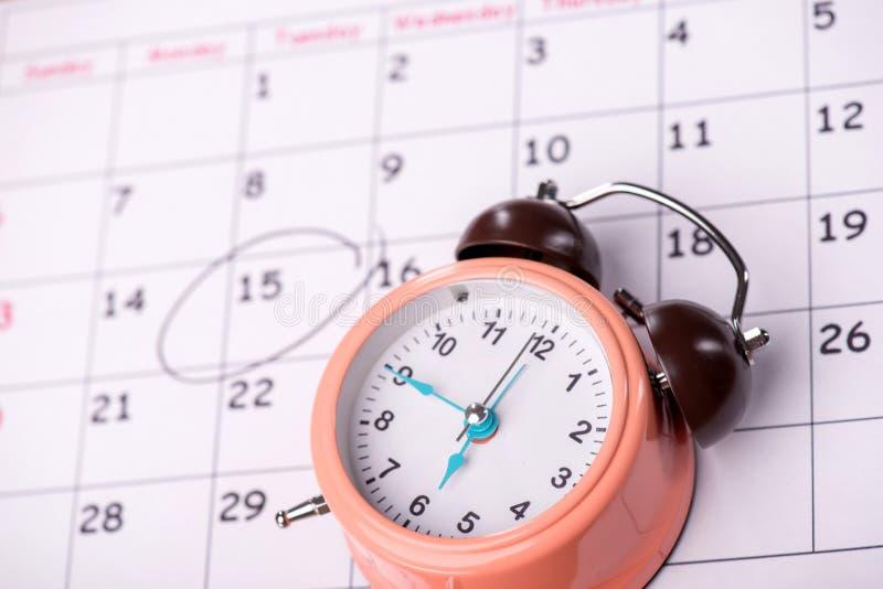 Close-up photo of calendar with a datum circled. Close-up top-view photo of calendar with a datum circled with a black marker, with selective focus on an alarm royalty free stock photos