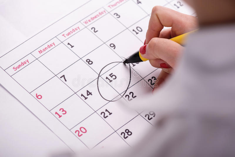 Close-up photo of calendar with a datum circled. Close-up top-view photo of calendar with a datum circled by young woman with red nails with a back marker royalty free stock image