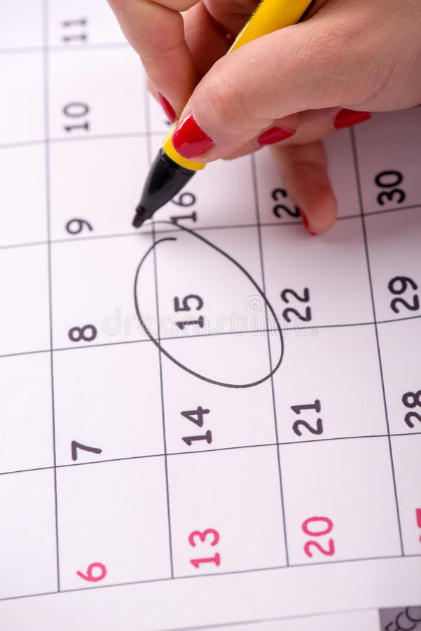 Close-up photo of calendar with a datum. Close-up top-view photo of calendar with a datum circled by young woman with red nails with a back marker, concept of royalty free stock photo
