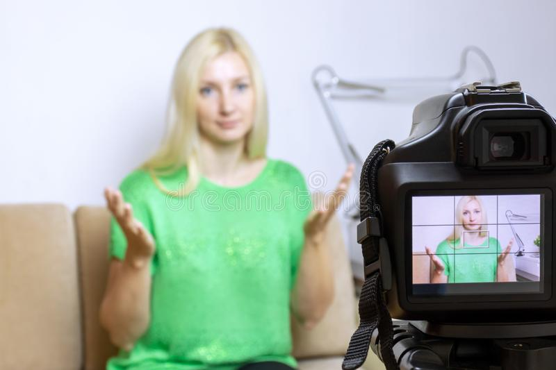 Close up photo of camera on tripod with young woman on LCD screen and blurred scene on background. Female video blogger recording stock photography