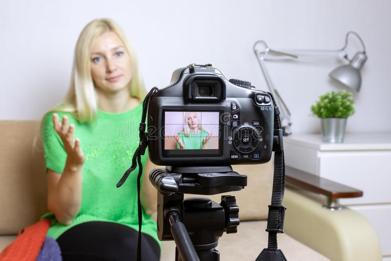 Close up photo of camera on tripod with young womanon LCD back screen and blurred scene on background. Female video blogger record royalty free stock photos