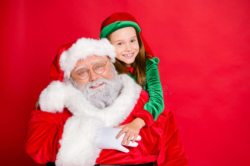 Close up photo of charming little elf helper in green hat headwear hugging piggyback her funny santa claus wearing stock photography