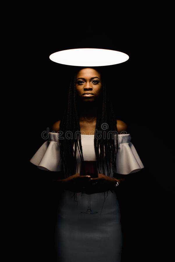 Close up photo of charming, touching, tender, beautiful african woman standing under bright light and looking at the royalty free stock image