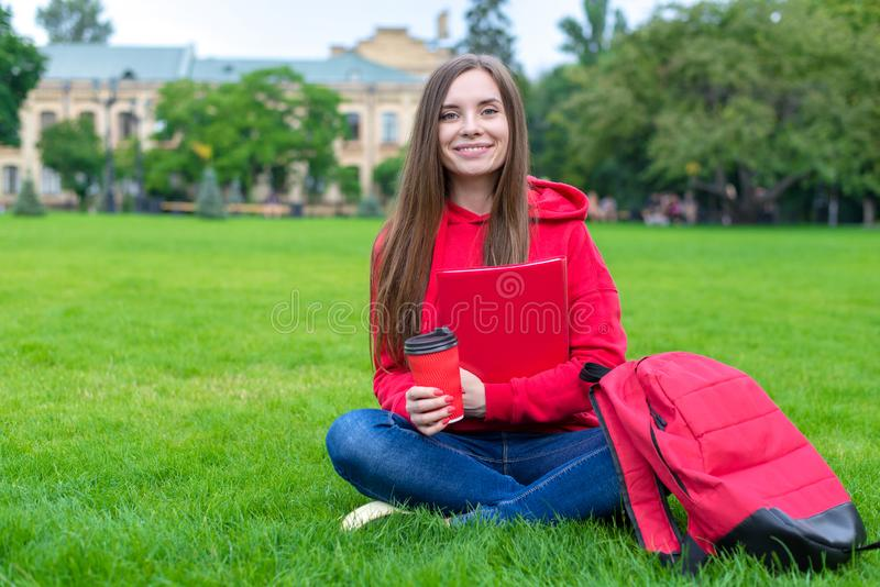 Close up photo of cheerful excited teen teenager hipster holding takeaway mug with tea  and copybook.  royalty free stock images