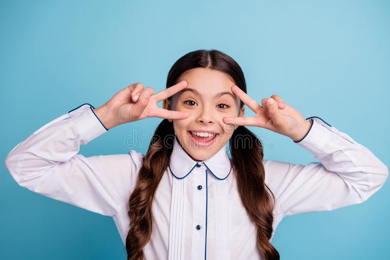 Close up photo of cheerful kid make v-signs laugh feel rejoice isolated over blue background. Close up photo of cheerful kid make v-signs laugh, feel rejoice stock image