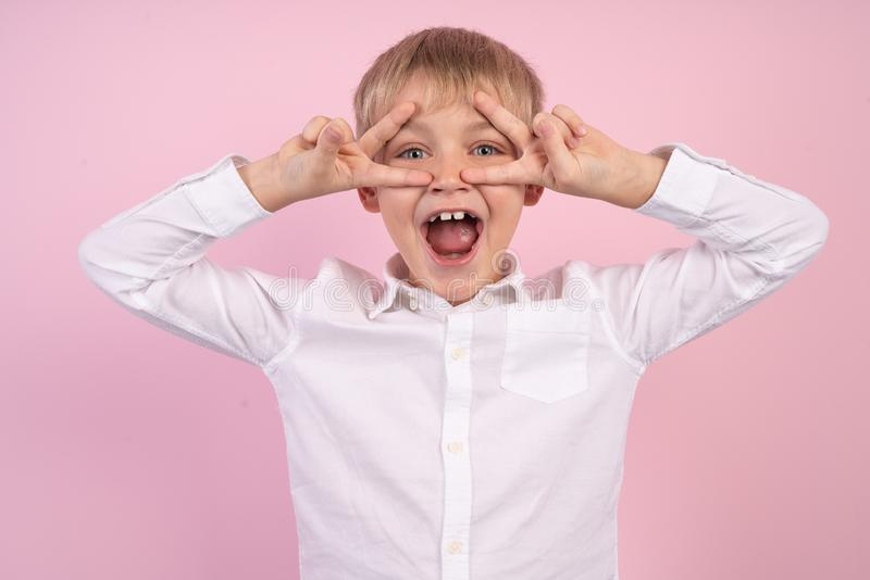 Close up photo of cheerful kid make victory signs laugh feel rejoice isolated over pink background.  royalty free stock photo