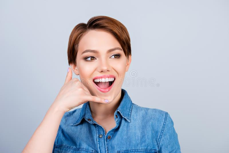 Close up photo of cheerful optimistic smiling young woman in casual clothes showing a gesture 'call me' against gray background royalty free stock photo