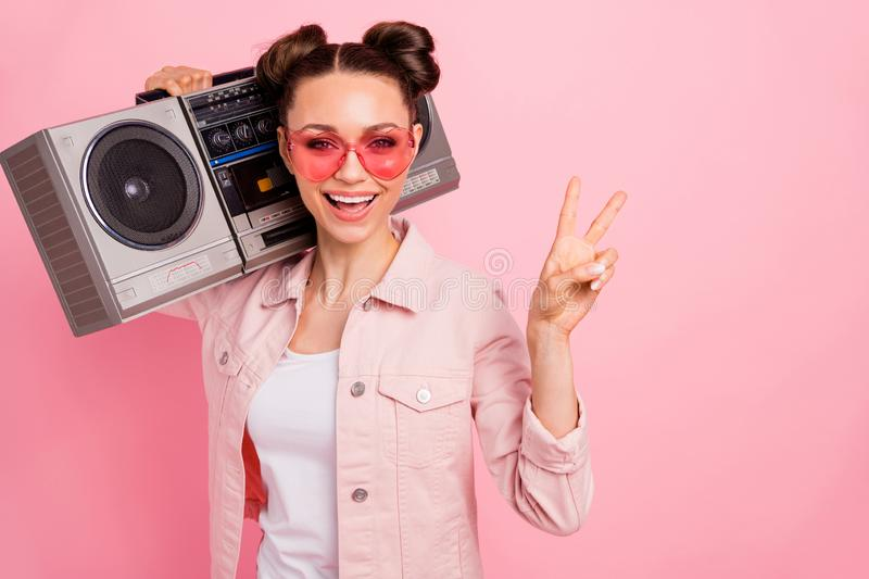 Close up photo of cheerful teen making v-signs holding boom box wearing jacket isolated over pink background. Close up photo of cheerful teen making v-signs stock photography