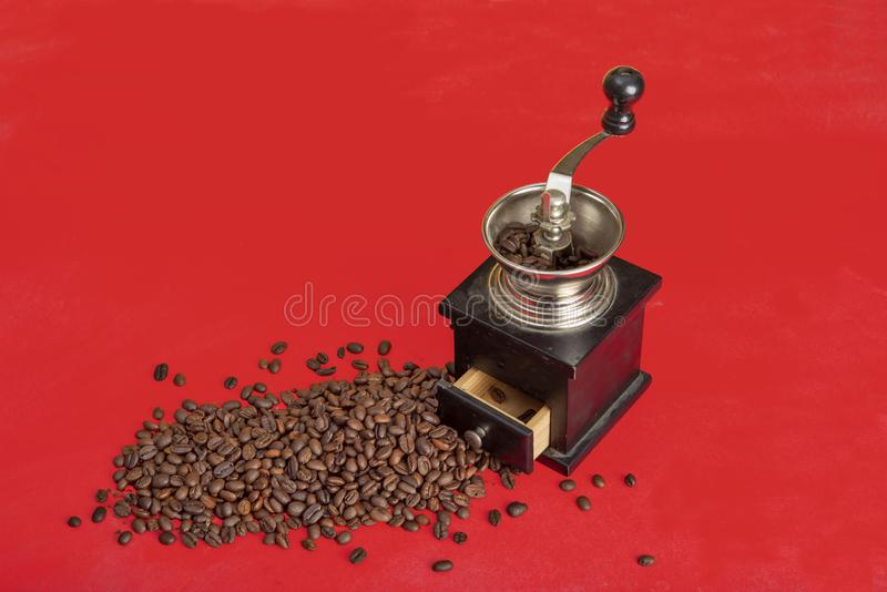 Close up photo of coffee beans with grinder on red backgorund. Close up photo of coffee beans with grinder on red background royalty free stock photos
