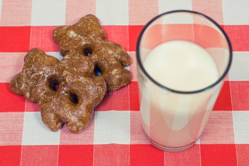 Close up photo of cookies and glass og milk on checkered tablecloth stock photo