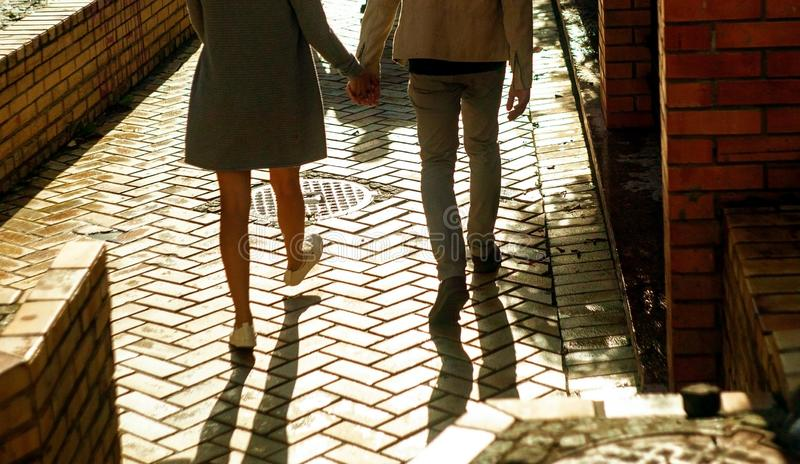 Close up photo of couple`s legs  walking on street at sunset. royalty free stock images