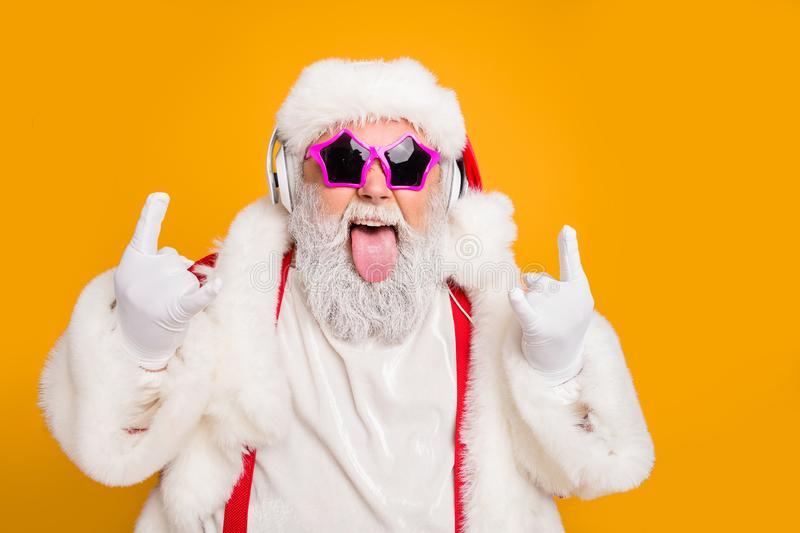 Close up photo of crazy funny hipster santa claus show horns sign tongue-out want rock-and-roll concert instead x-mas. Close up photo of crazy funny hipster stock photo