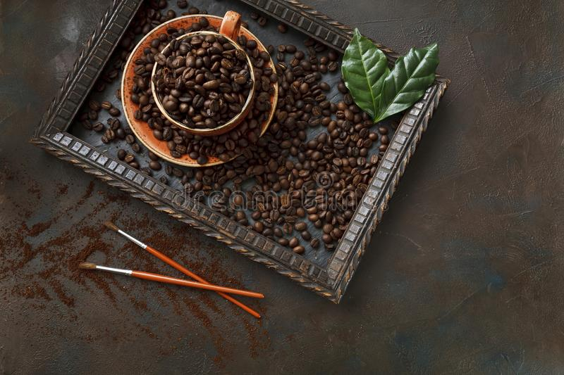 Close-up photo of cup with aroma coffee beans and fresh green le stock photo