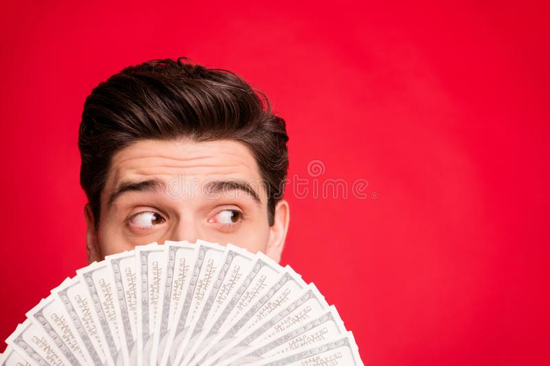Close up photo of curious man hiding behind his money and watching someone away while isolated with red background. Close up photo of curious man hiding, behind royalty free stock image