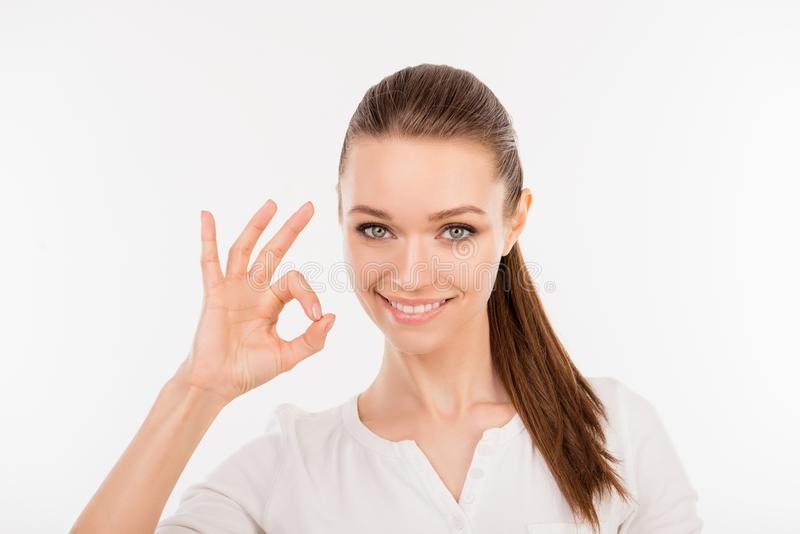 Close up photo of cute young happy woman showing ok-sign against stock photography