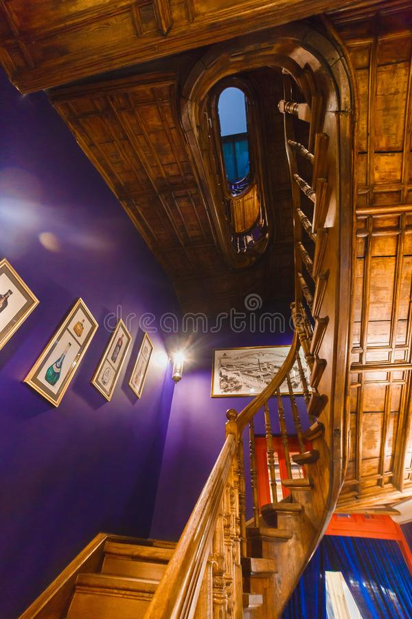 The close-up photo of the dark wooden staircases next to the purple wall decorated with paintings. stock image