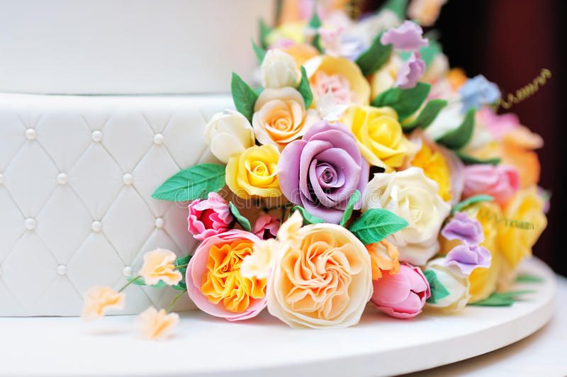 Close up photo of delicious wedding or birthday cake. Close up photo of delicious luxury white wedding or birthday cake decorated with cream colorful flowers stock images