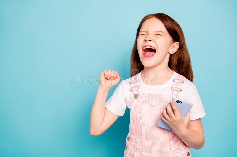 Close up photo of delighted kid raise hands scream yeah close eyes have device wear stylish trendy overalls isolated stock photography