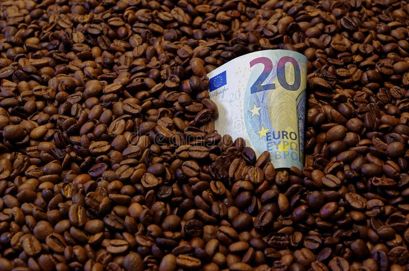 20 Euro banknote in the roasted coffee beans. Close up photo of 20 Euro banknote in the roasted coffee beans stock photo