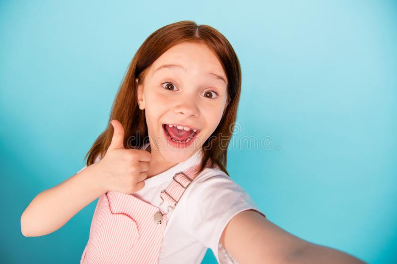 Close up photo excited charming kid make photo video call laugh wear overalls isolated over blue background. Close up photo excited, charming kid make photo stock photos