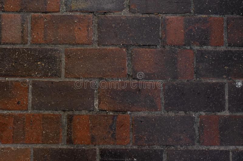 Exterior wall with lines of concrete between brown and black building bricks. Close up photo of the exterior wall with lines of concrete between rectangle brown stock photo