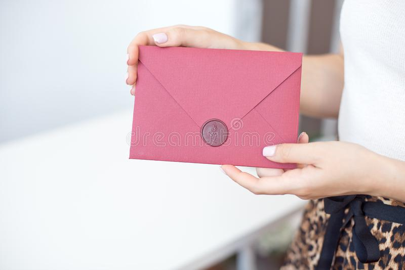 Close-up photo of female hands holding a silver invitation envelope with a wax seal, a gift certificate, a postcard, a wedding. Invitation card, background stock photo