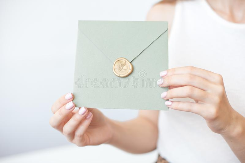 Close-up photo of female hands holding a silver invitation envelope with a wax seal, a gift certificate, a postcard, a wedding. Invitation card, background stock images