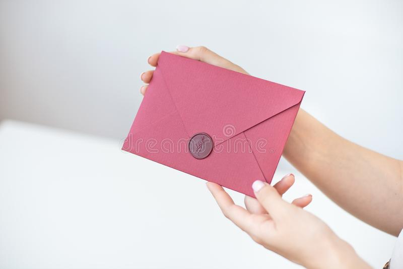 Close-up photo of female hands holding a silver invitation envelope with a wax seal, a gift certificate, a postcard, a wedding. Invitation card, background royalty free stock image