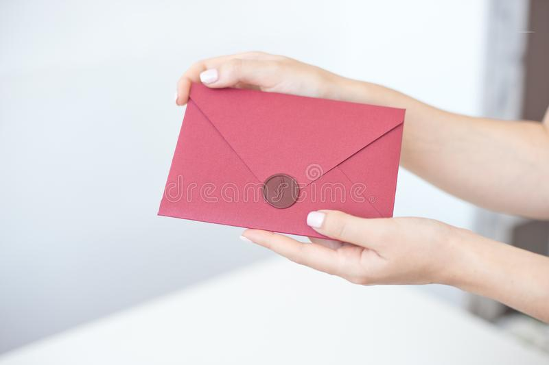 Close-up photo of female hands holding a silver invitation envelope with a wax seal, a gift certificate, a postcard, a wedding. Invitation card, background royalty free stock photos