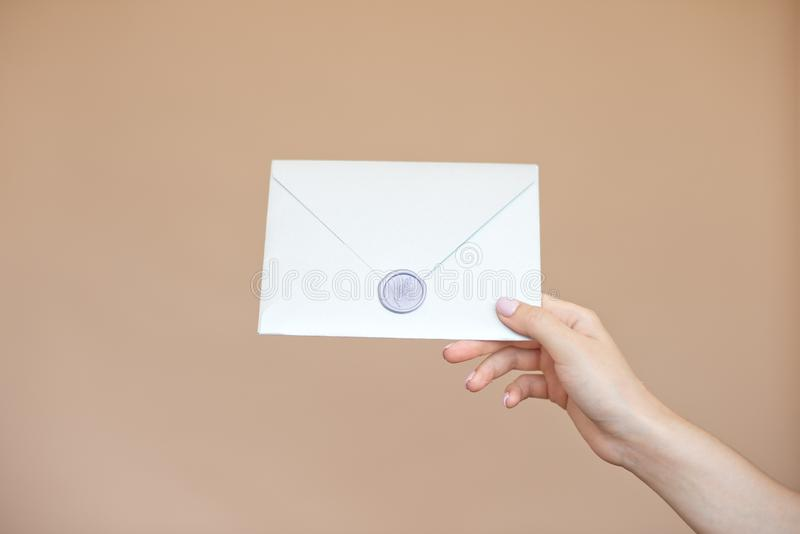 Close-up photo of female hands with wax seal with invitation envelope, gift certificate, postcard, wedding invitation card. Background, paper, blank, white royalty free stock images