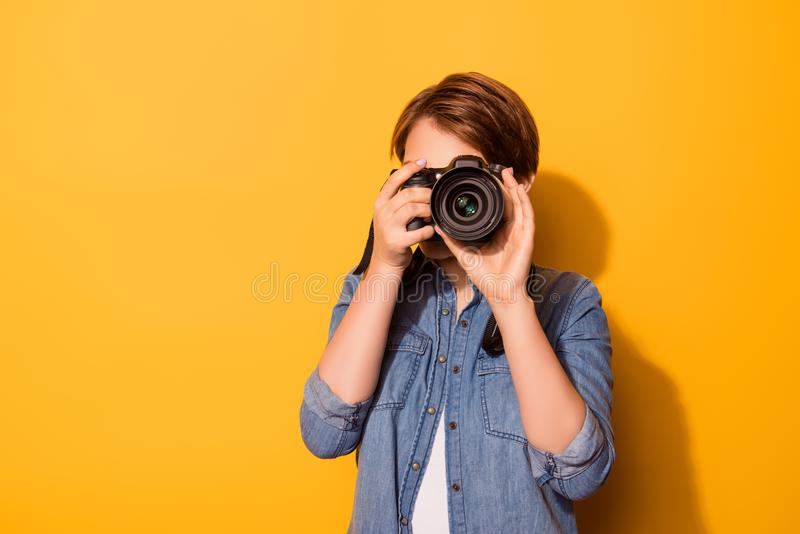 Close up photo of female photographer photographing with a camera in casual clothes on the bright yellow background royalty free stock photography