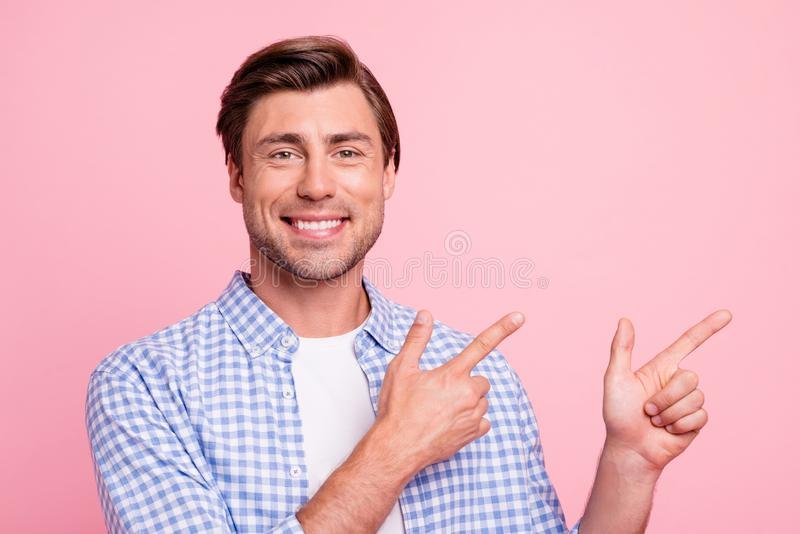 Close up photo of fine brunet smiling glad he him his man arm finger showing to empty space on sale discount wearing. Casual plaid shirt white t-shirt outfit stock image