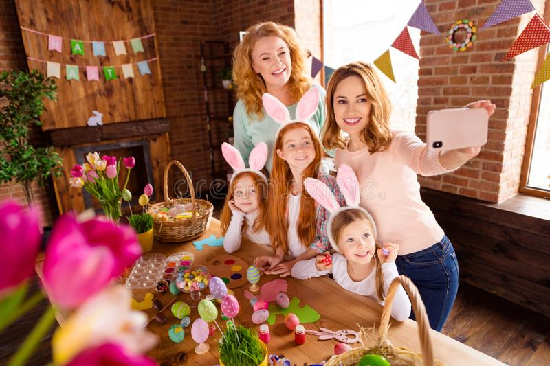 Close up photo foxy three small girls children day easter two mommy pretty table full handmade craft big wooden have stock photos