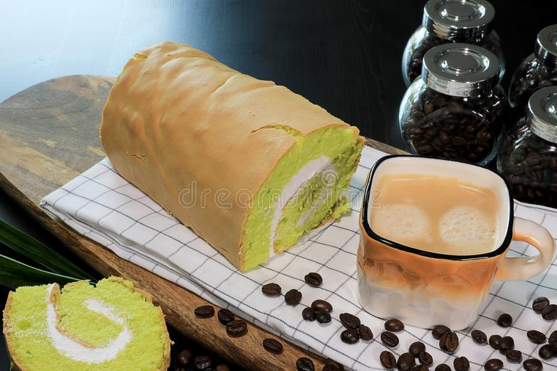 Close-up photo Fresh Hot Coffee in the brown and white color cup with coffee beans, and Pandanus Yam Roll Cake with white cream stock photo