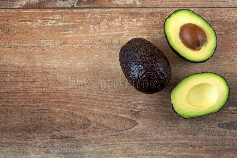 Close-up photo of fresh sliced avocados, brown seeds visible on brown wooden background. Top view. Copy space. stock images