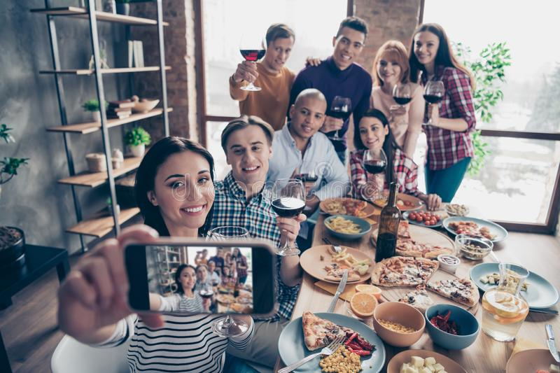 Close up photo friendly event together diversity different race guys raise glasses red beverage telephone make take stock images