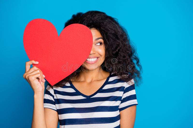Close up photo of funky cheerful mulatto girl hold big red papercard heart close cover face look romantic boyfriend. Close up photo of funky cheerful mulatto stock photography