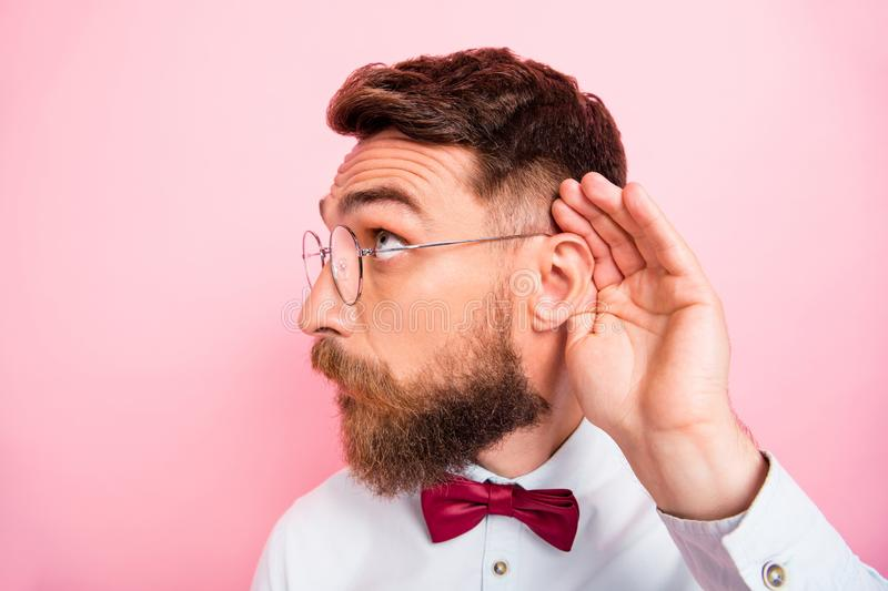Close-up photo of funny funky smart concentrated hipster gentleman holding palm near ear catching familiar sound. Close-up photo of funny funky smart royalty free stock image
