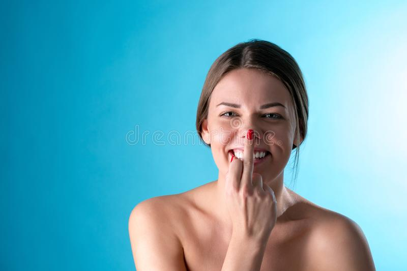 Close-up photo of funny young brunette woman showing middle fingers on hand, looking at camera, on blue royalty free stock images