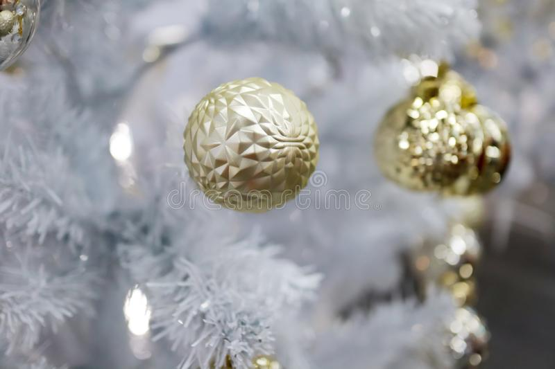 Close up photo of golden ball and light garland. Close up photo of golden ball and light garland on white Christmas tree stock photo