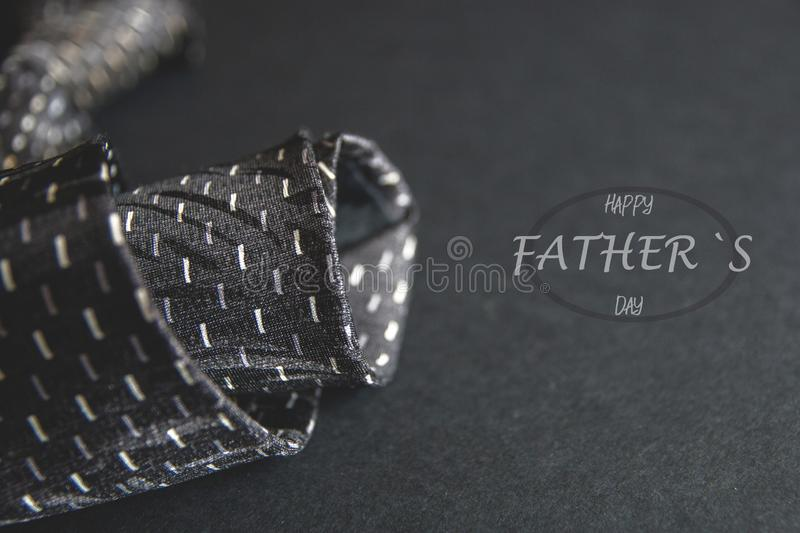 Close - up photo gray men`s tie. Father`s day inscription for the holiday. Text for holiday card or banner on black background royalty free stock image