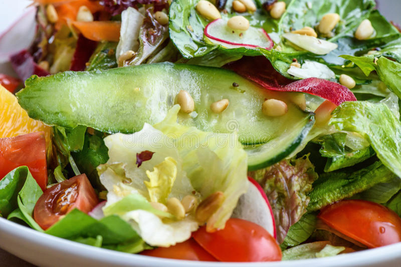 Close up photo of green healthy salad. With ruccola, tomatoes, cucumbers, beet and seeds royalty free stock photography