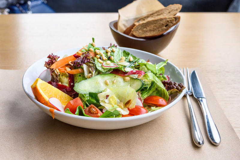 Close up photo of green healthy salad. With ruccola, tomatoes, cucumbers, beet and seeds, brown bread, fork and knife on a wooden restaurant table stock images