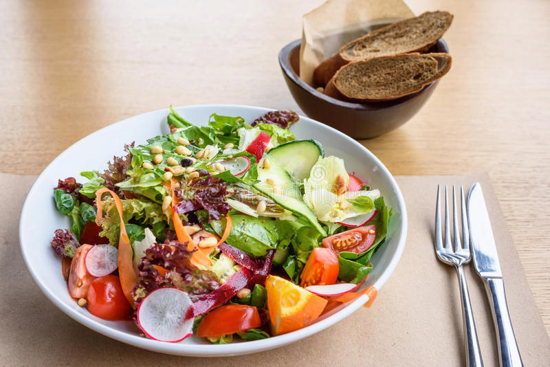 Close up photo of green healthy salad. With ruccola, tomatoes, cucumbers, beet and seeds, brown bread, fork and knife on a wooden restaurant table stock photo