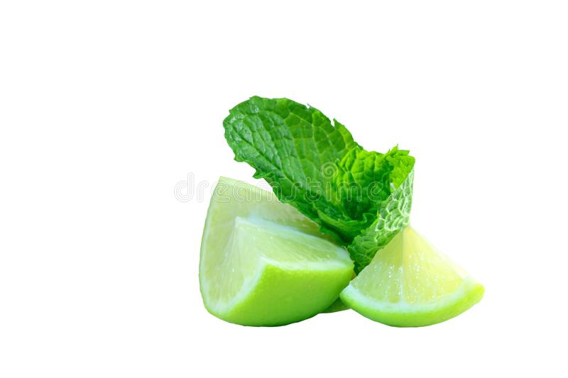 Close-up photo of green-yellow lime pieces and mint leaves; juicy pieces of fruit and bright colours isolated on white background. A macro photo of green lime stock photo