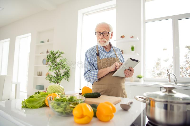 Close up photo grey haired he his him grandpa hands arms e-reader noticing changes improving family traditional holiday. Dish wear specs casual checkered plaid stock photo