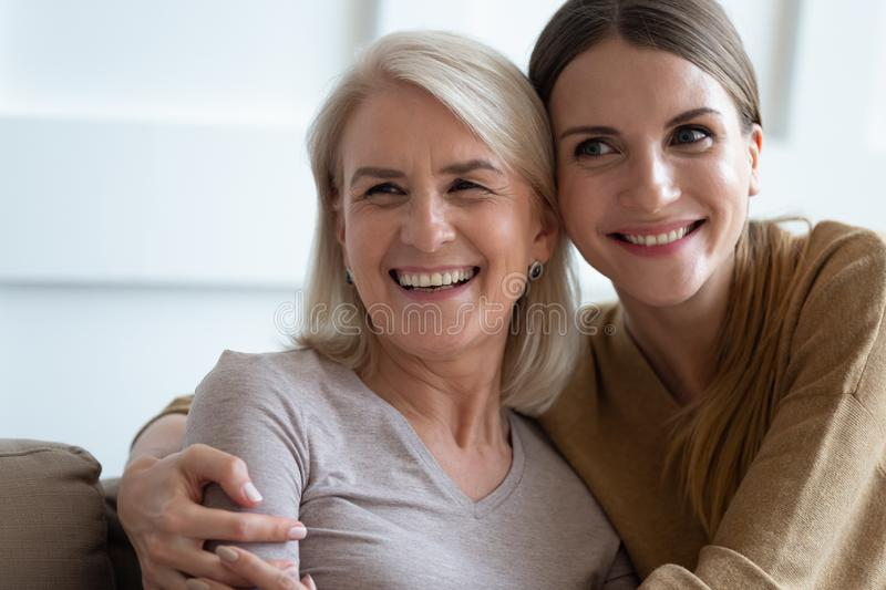 Close up photo adult daughter cuddles old mother. Close up photo grown up adult 30s daughter embracing elderly blonde mother diverse women sit on couch looking stock images