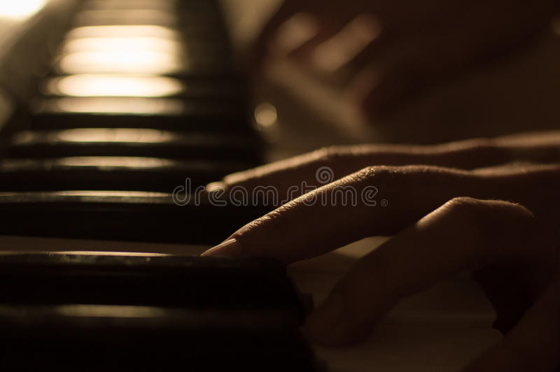 Close-up photo of a hand playing the piano keys. Concept: Music creating, composing, lyrics, performance. Close-up soft focused atmospheric photography of a hand royalty free stock image